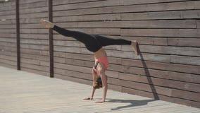 Vrouw het praktizeren de yogahandstand stelt op muur bij zonnige dag stock footage