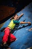 Vrouw het praktizeren inklimming op een rotsmuur stock foto