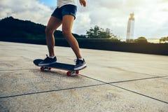 Vrouw het praktizeren met skateboard Stock Foto's
