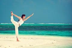 Vrouw het praktizeren yoga bij kust Royalty-vrije Stock Foto's