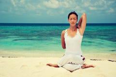 Vrouw het praktizeren yoga bij kust Stock Fotografie