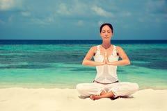 Vrouw het praktizeren yoga bij kust Stock Afbeeldingen