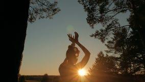 Vrouw het praktizeren yoga in bos bij zonsondergang stock footage