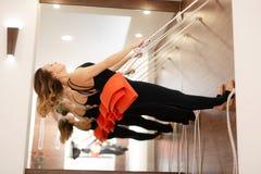 Vrouw het praktizeren yoga die op kabels zich in gymnastiek uitrekken Pasvorm en wellnesslevensstijl royalty-vrije stock foto