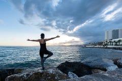 Vrouw het praktizeren yoga die het overzees op een bewolkte dag onder ogen zien royalty-vrije stock afbeelding