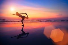 Vrouw het praktizeren yoga op het strand bij zonsondergang Royalty-vrije Stock Afbeeldingen