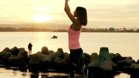 Vrouw het praktizeren yoga op het strand bij zonsondergang stock video