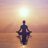 Vrouw het praktizeren yoga, silhouet op het strand bij zonsondergang Royalty-vrije Stock Foto's