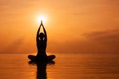 Vrouw het praktizeren yoga, silhouet op het strand bij zonsondergang Stock Foto