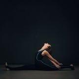 Vrouw het praktizeren yoga tegen een donkere muur royalty-vrije stock foto