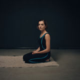Vrouw het praktizeren yoga tegen een donkere texturized muur Royalty-vrije Stock Afbeelding