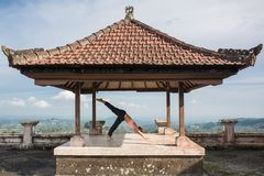 Vrouw het praktizeren yoga in traditionele balinessegazebo royalty-vrije stock afbeelding