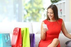 Vrouw in het rode kopen met een slimme telefoon Stock Foto's