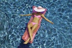Vrouw in het roze bikini drijven royalty-vrije stock afbeelding