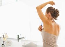 Vrouw het scheren oksel in badkamers Stock Afbeeldingen
