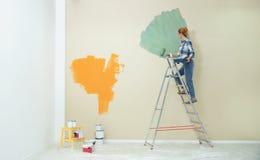 Vrouw het schilderen muur binnen Huisreparatie stock foto's