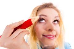 Vrouw het schilderen wenkbrauwen die regelmatig potlood gebruiken stock fotografie