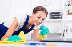 Vrouw het schoonmaken in bedrijfbureau stock afbeelding