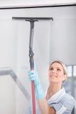 Vrouw het Schoonmaken met Rubbervensterreinigingsmachine Royalty-vrije Stock Foto's