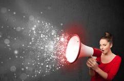 Vrouw het schreeuwen in megafoon en de gloeiende energiedeeltjes exploderen Stock Foto