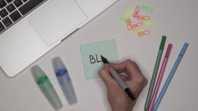Vrouw het schrijven BLOG op zelfklevende blocnote Laptop en kantoorbehoeften op de lijst stock video