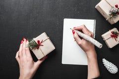 Vrouw het schrijven brief aan Santa Claus bij zwarte lijst Kerstmis en Gelukkige Nieuwjaarskaart Vlak leg, hoogste mening Royalty-vrije Stock Afbeelding