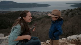 Vrouw het spelen gitaar en weinig jongen op klip in donkere dag stock footage