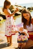 Vrouw het spelen met kinderen op strand Stock Afbeeldingen