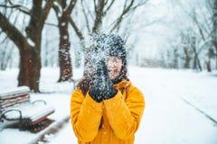 Vrouw het spelen met sneeuw in gesneeuwd stadspark royalty-vrije stock foto's