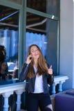 Vrouw het spreken door smartphone en het tonen beduimelen omhoog Stock Fotografie