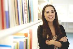 Vrouw het stellen in bibliotheek met gekruiste wapens Stock Afbeelding
