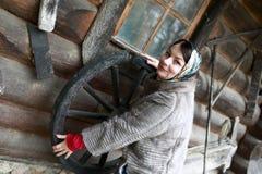 Vrouw het stellen met oud houten wiel stock fotografie