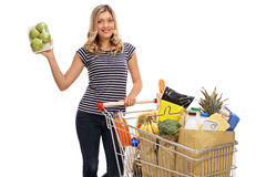 Vrouw het stellen met pak van appelen en boodschappenwagentje Royalty-vrije Stock Foto
