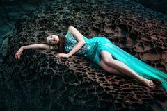 Vrouw het stellen op een strand met rotsen Royalty-vrije Stock Afbeelding