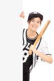 Vrouw in het stellen van honkbaljersey achter een paneel Stock Foto's
