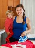 Vrouw het strijken bij strijkplank in huis Royalty-vrije Stock Afbeeldingen