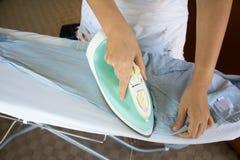 Vrouw het strijken overhemd op strijkplank Stock Afbeelding