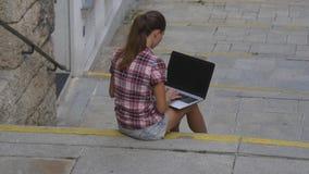 Vrouw het typen op laptop toetsenbordzitting op de treden stock video