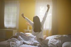 Vrouw het uitrekken zich in bed na kielzog omhoog royalty-vrije stock fotografie