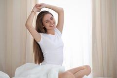 Vrouw het uitrekken zich in bed na kielzog omhoog, ingaand een dag gelukkig en na goede nachtslaap die wordt ontspannen Zoete goe stock afbeelding