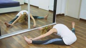 Vrouw het uitrekken zich dichtbij spiegel bij haar flat Het concept een gezonde levensstijl, niet een professionele sport stock video