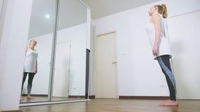Vrouw het uitrekken zich dichtbij spiegel bij haar flat Het concept een gezonde levensstijl, niet een professionele sport stock footage
