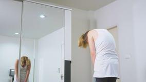 Vrouw het uitrekken zich dichtbij spiegel bij haar flat Het concept een gezonde levensstijl, niet een professionele sport stock videobeelden