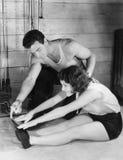 Vrouw het uitrekken zich met hulp van trainer Royalty-vrije Stock Afbeelding
