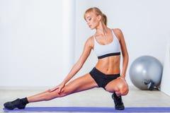 Vrouw het uitrekken zich spieren Stock Afbeeldingen