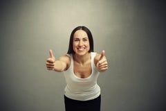 Vrouw het uitrekken zich vooruit en het tonen beduimelen omhoog Stock Foto