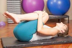 Vrouw het uitrekken zich in yoga Stock Fotografie