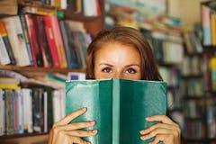 Vrouw het verbergen achter het groene boek Royalty-vrije Stock Afbeelding