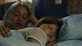 Vrouw het vertellen verhaal aan meisje in bed stock footage