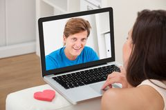Vrouw het video thuis babbelen met vriend op laptop Stock Fotografie